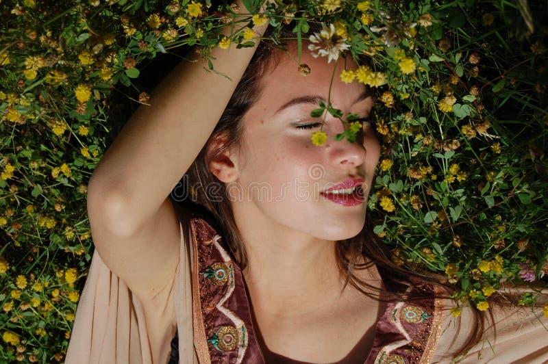 放置在草的女孩享受夏令时 库存照片