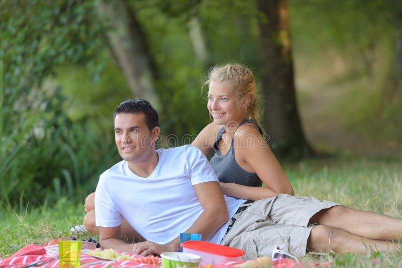 放置在草的年轻夫妇 免版税库存照片