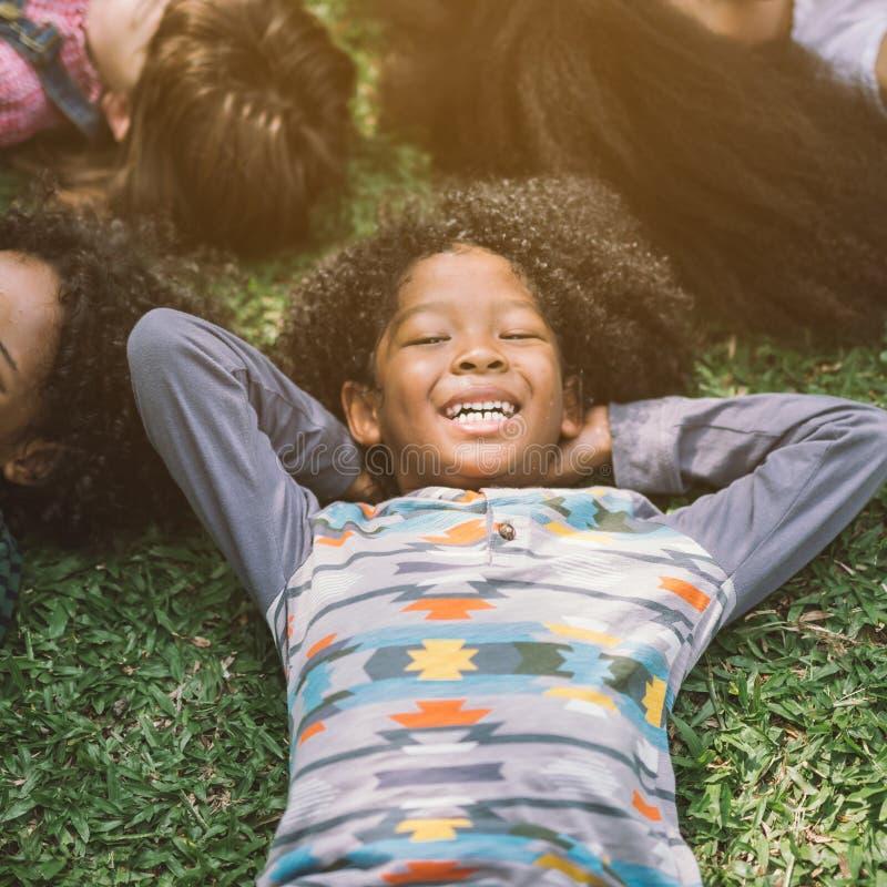 放置在草的愉快的儿童孩子 免版税库存图片