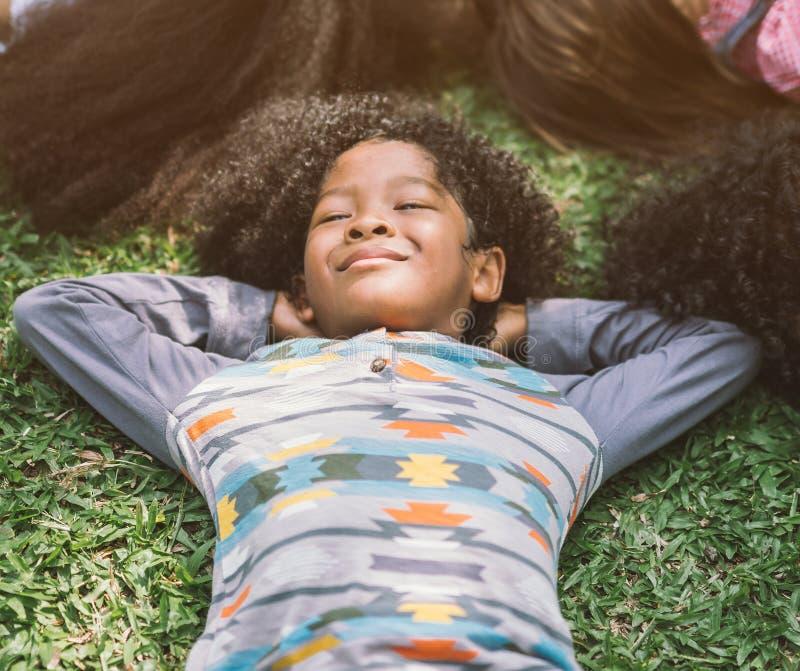 放置在草的愉快的孩子在公园 免版税库存图片