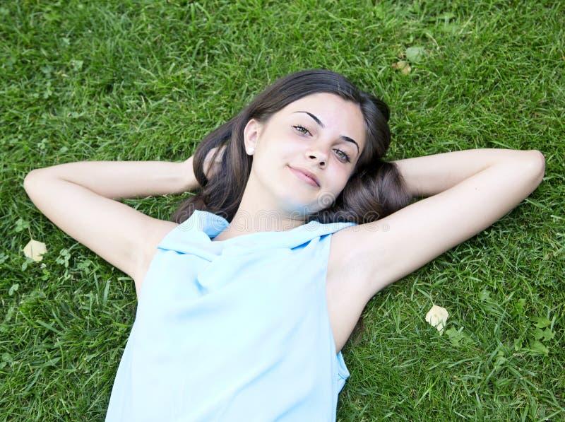 放置在草的松弛女孩 免版税库存照片