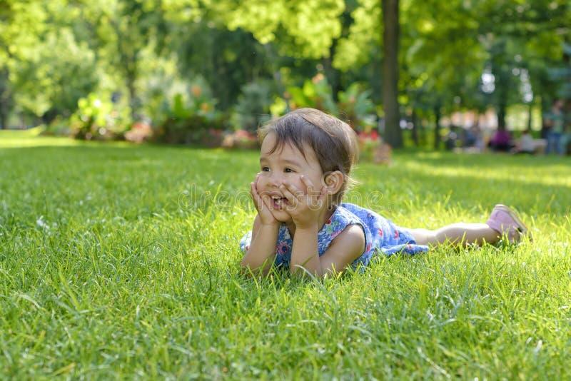 放置在草的逗人喜爱的小女孩在一个夏日 图库摄影