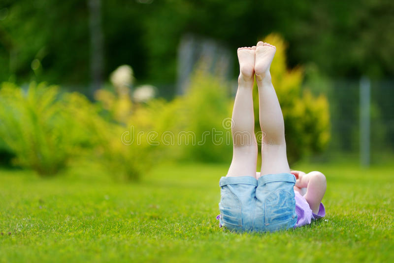 放置在草的逗人喜爱的小女孩 免版税库存图片