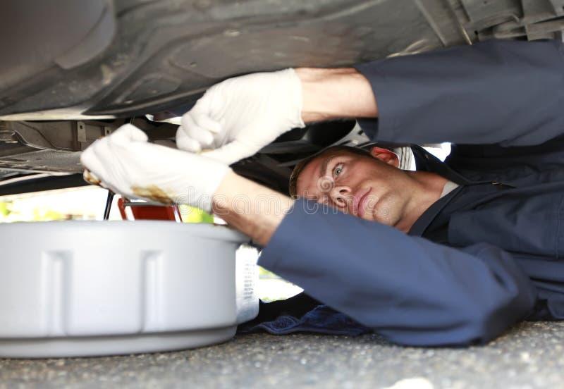 放置在车之下的人改变的汽车油。 免版税库存照片