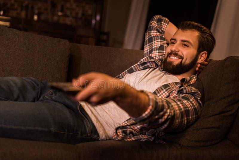 放置在长沙发和观看的电视的年轻人 库存照片