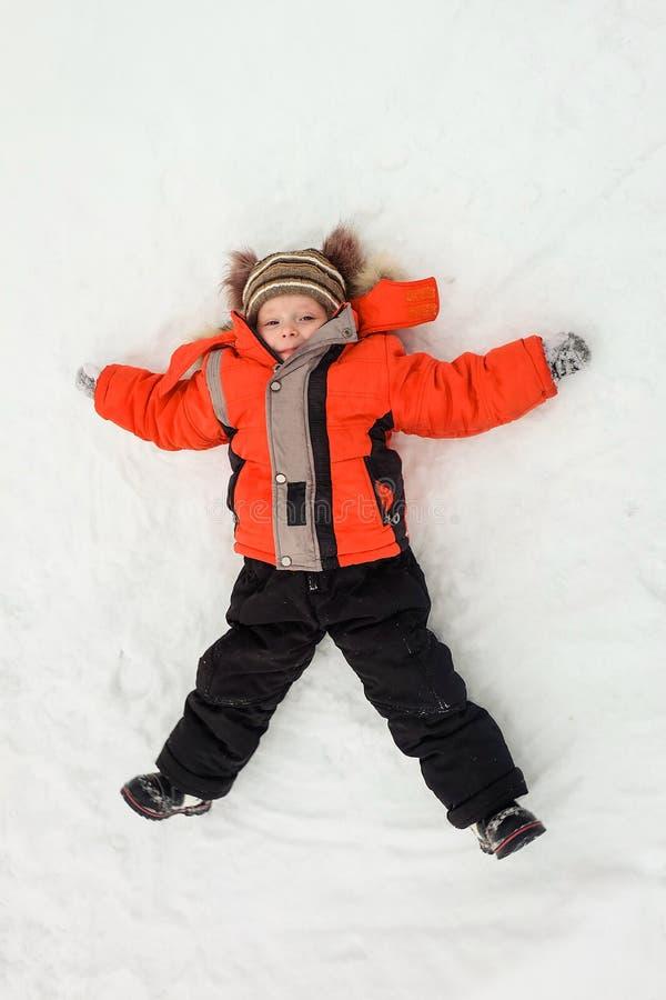 放置在雪和做雪天使的愉快的小男孩孩子 库存照片