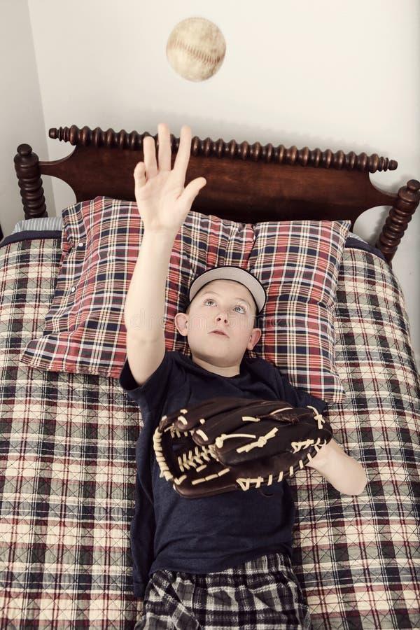 放置在他的床等待的棒球季节的男孩 免版税图库摄影