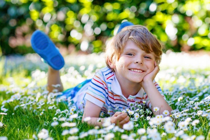 放置在绿草的逗人喜爱的孩子男孩在夏天 免版税库存照片