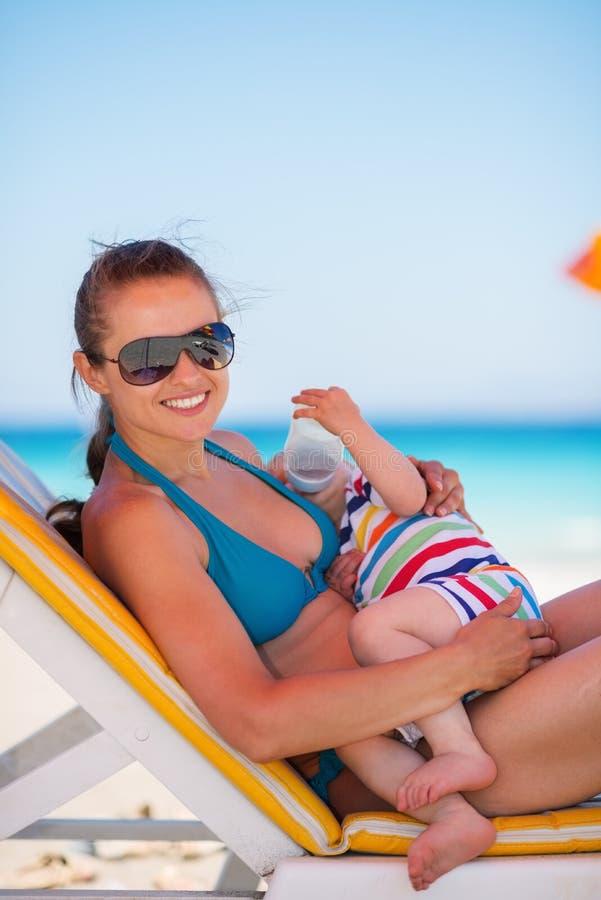 放置在sunbed和暂挂的婴孩的母亲 库存照片