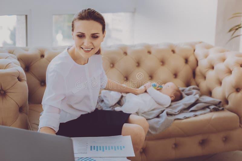 放置她小孩睡觉的产假的年轻工作母亲 库存图片