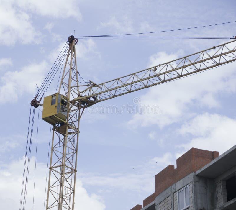 放置户外站点的砖建筑 建筑用起重机和高层建筑物建设中反对蓝天 库存图片