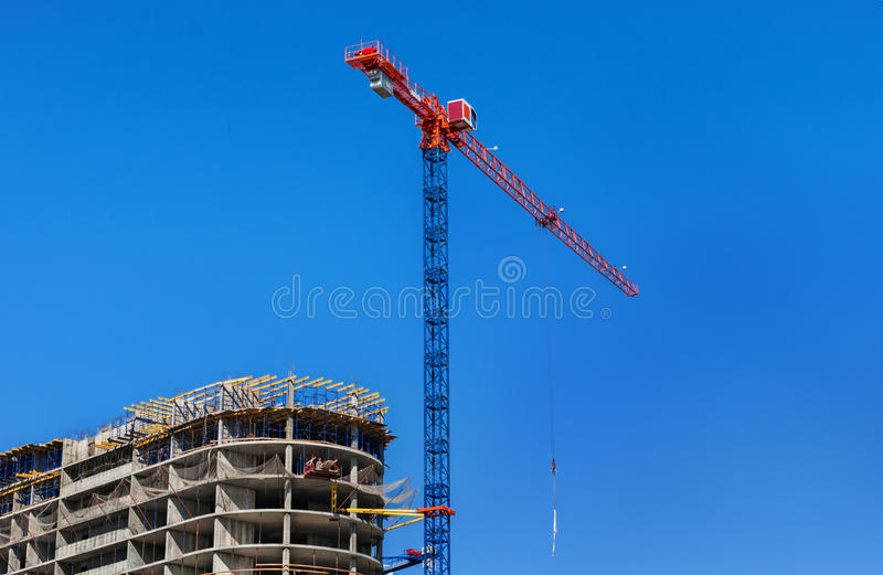 放置户外站点的砖建筑 建筑用起重机和高层建筑物建设中反对蓝天 库存照片