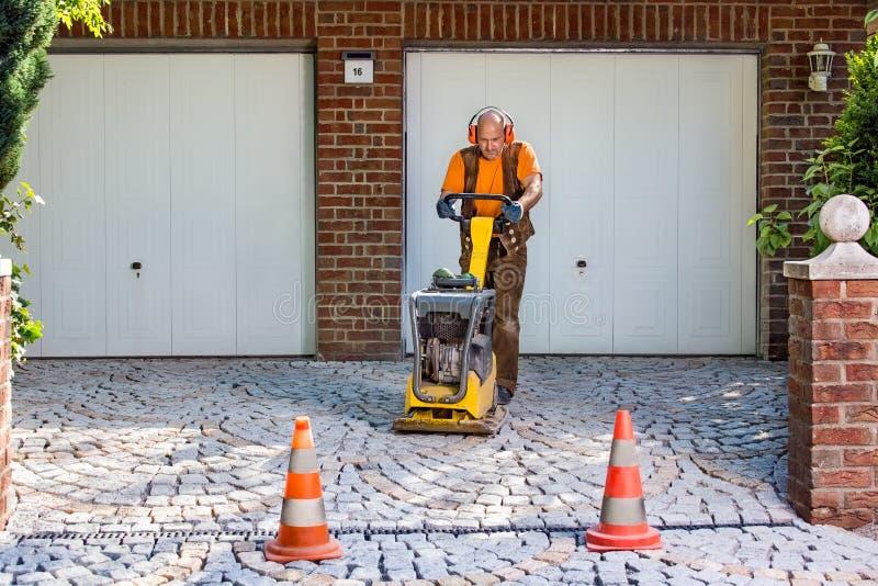 放置新的铺的砖的建造者或承包商 库存图片