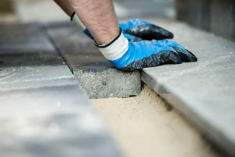 放置新的铺的砖的建造者 库存图片