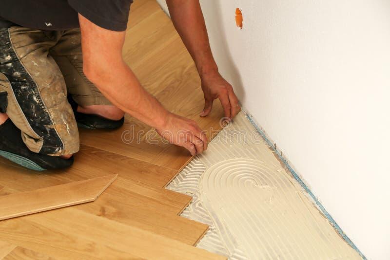 放置木条地板地板的工作者 安装木层压制品的地板的工作者 库存照片