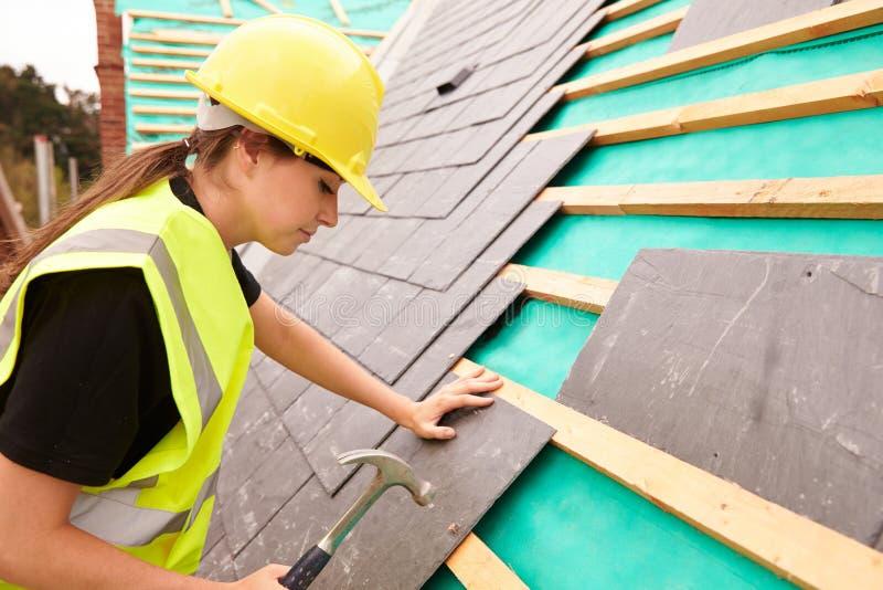 放置板岩瓦片的站点的女性建筑工人 图库摄影