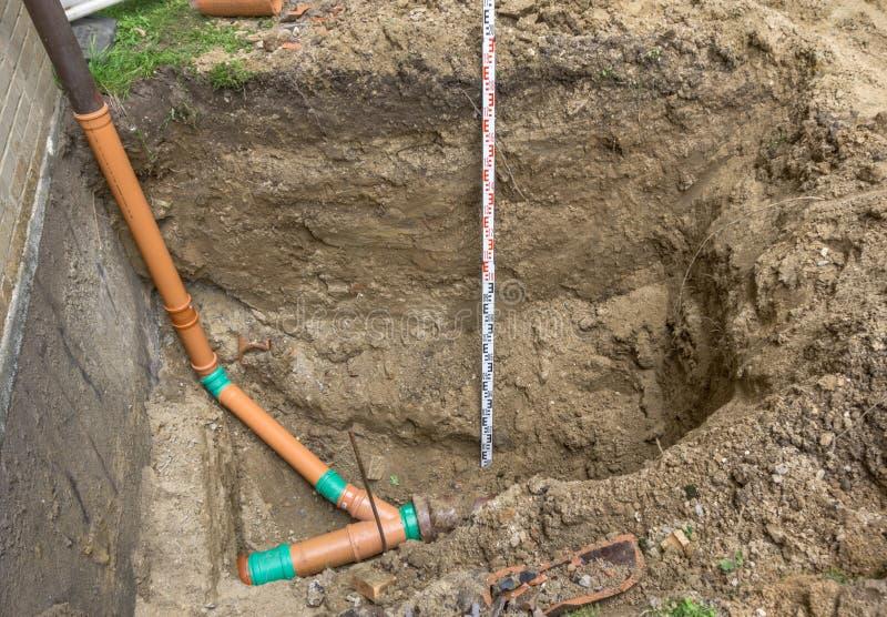 放置污水用管道输送在一个露台的房子的角落在德国 免版税库存照片