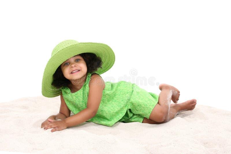 放置沙子年轻人的美丽的女孩 免版税图库摄影