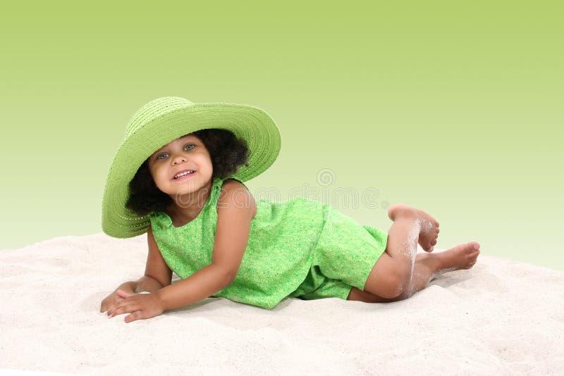 放置沙子年轻人的美丽的女孩 免版税库存照片