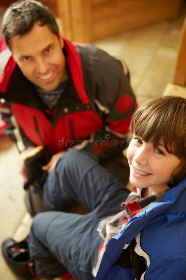 放置温暖的室外衣裳的父亲帮助的儿子 库存照片