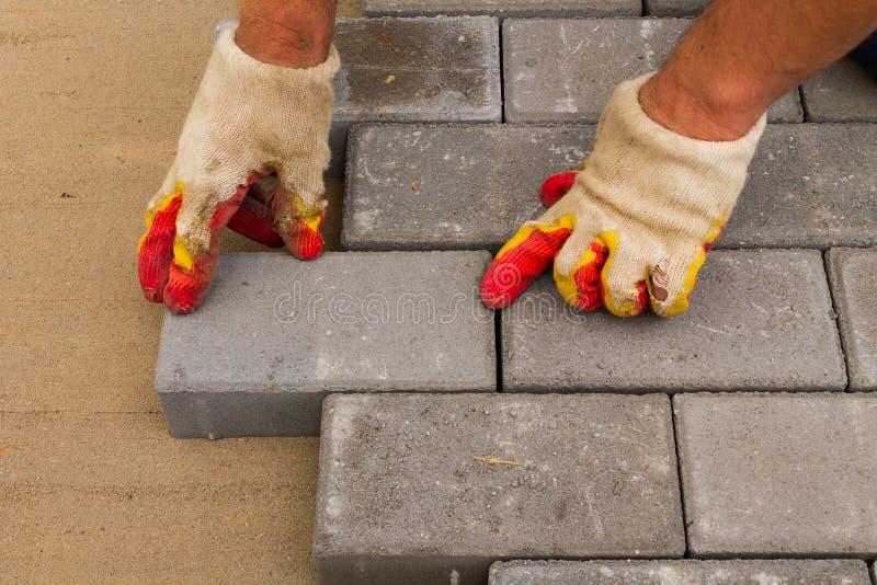 放置灰色具体铺路板在房子庭院车道露台 专业工作者瓦工安装新的瓦片或 库存照片