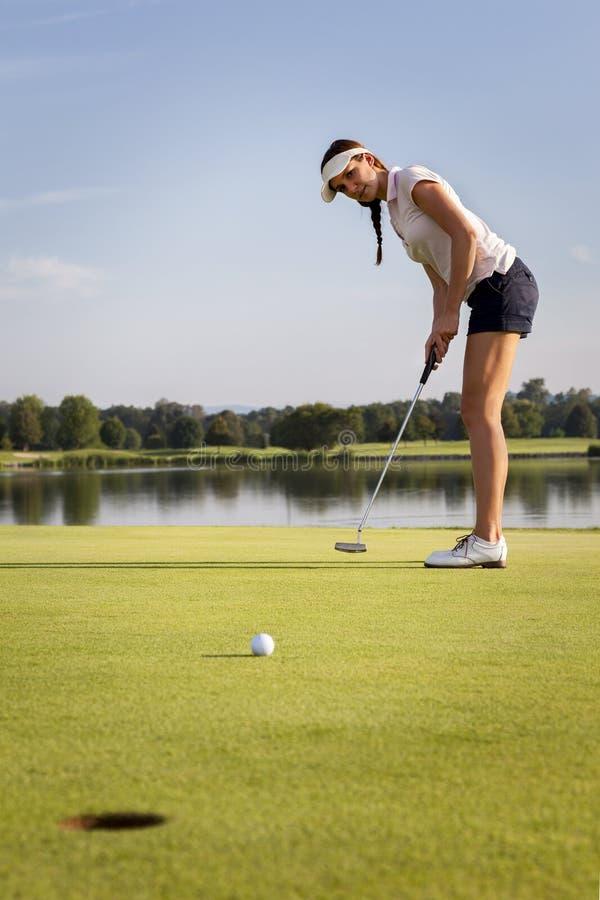 放置球的女孩高尔夫球运动员在绿色。 库存图片