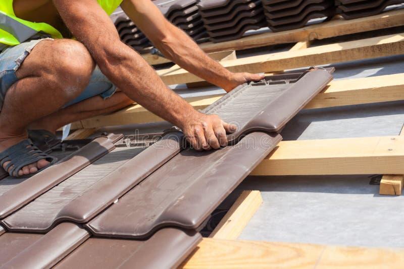 放置瓦片的盖屋顶的人的手在屋顶 安装自然红色瓦片 免版税库存图片