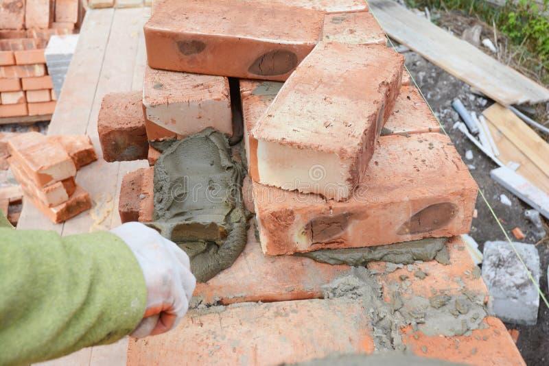 放置砖的专业建筑工人在房子建造场所 免版税图库摄影