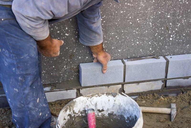放置砖的建造者,修建墙壁 库存照片