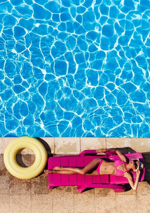 放置美丽的少妇在游泳池边sunbed 免版税库存图片