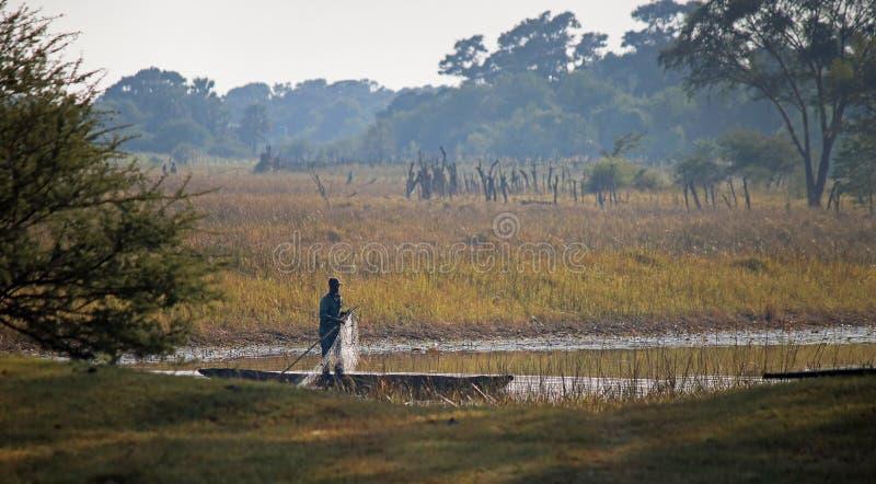 放置鱼网的观点的一位地方渔夫在从一条小船的一条河 免版税图库摄影
