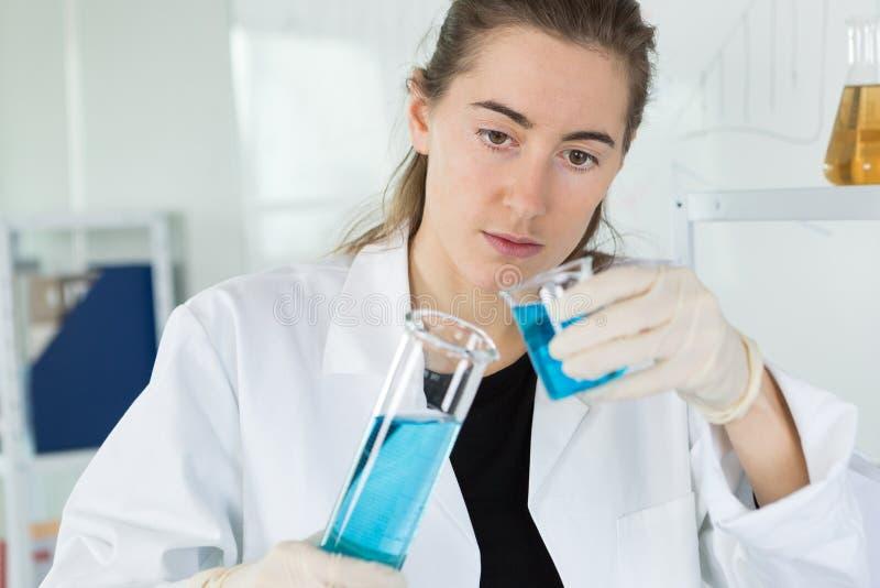 放蓝色液体的女性科学家入烧瓶 免版税库存图片