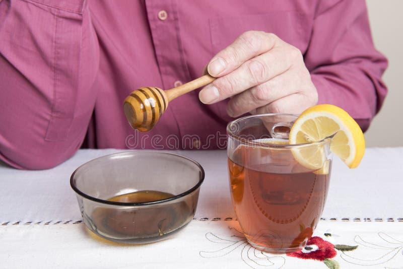 放蜂蜜的成熟人入一杯热水和柠檬 库存照片