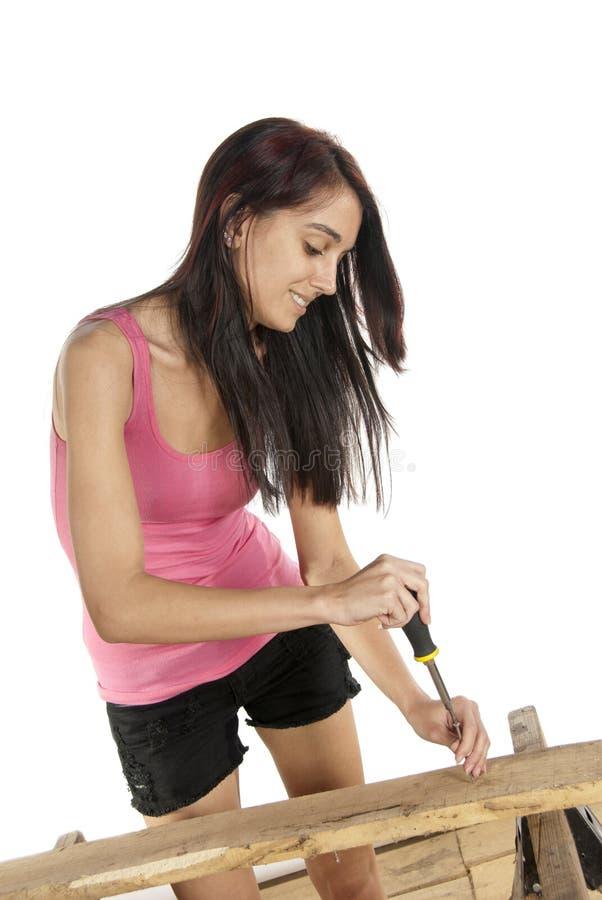 放螺丝的少妇螺丝刀入木头 免版税库存图片