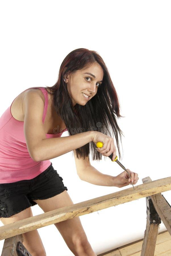 放螺丝的少妇螺丝刀入木头 免版税库存照片