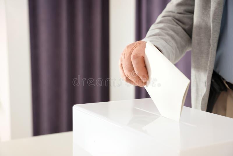 放选票的年长人入箱子在投票站 免版税库存图片