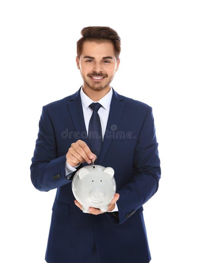 放金钱的年轻商人入存钱罐 免版税库存照片