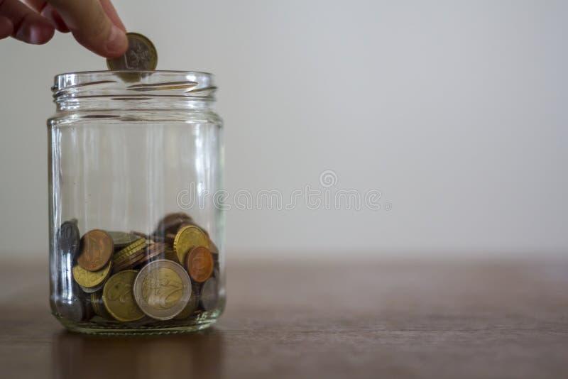 放金钱的手入有拷贝空间的玻璃瓶子 免版税库存图片