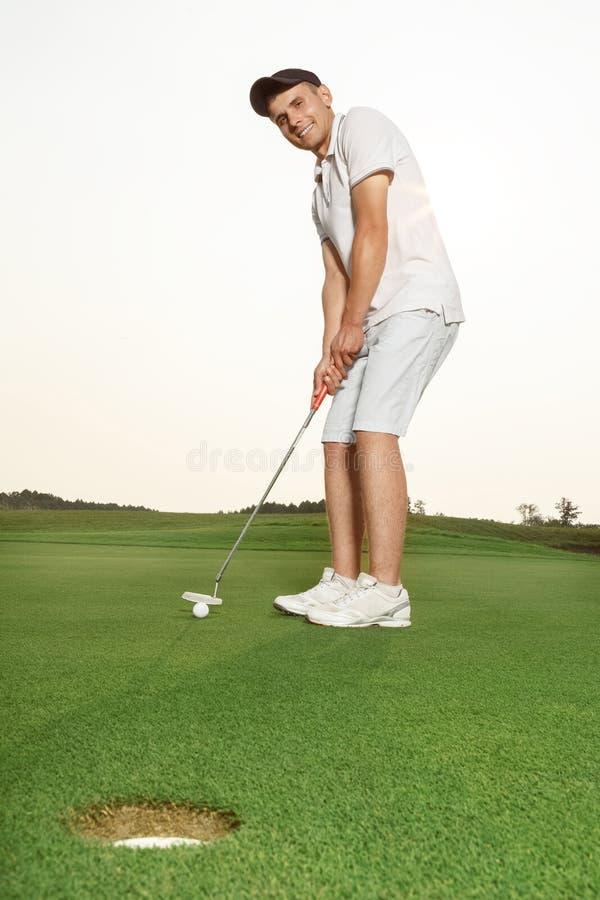 放高尔夫球的运动员入孔 免版税库存图片