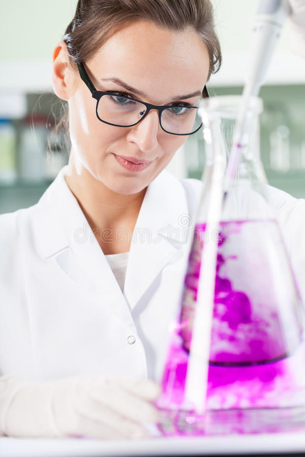 放紫罗兰色液体的科学家入烧瓶 图库摄影