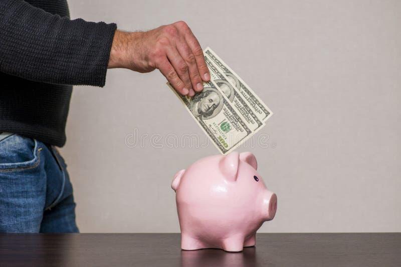放100美金的男性手入存钱罐 E 库存图片
