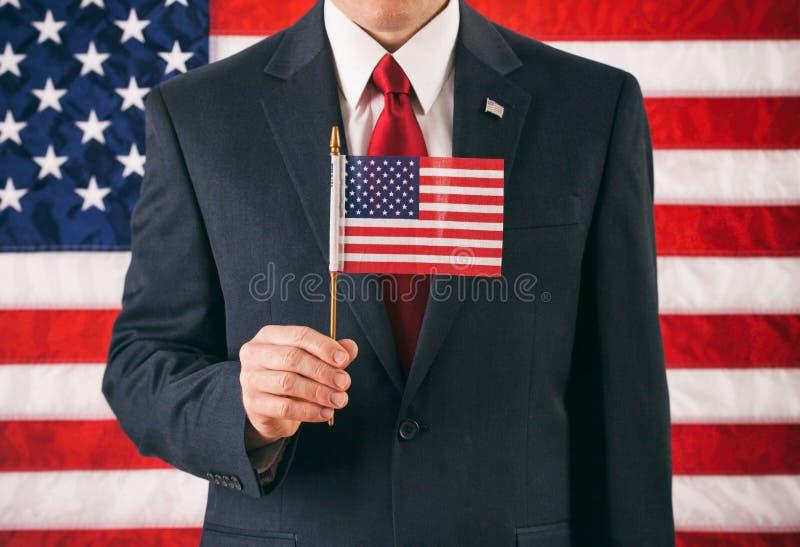 政客:拿着在棍子的人小美国旗子 库存图片