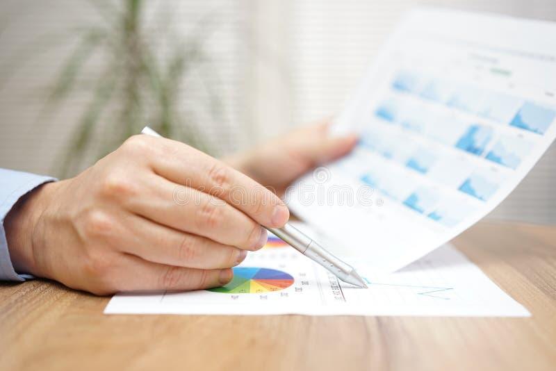 财政顾问是与图和图表的评估报告 免版税图库摄影