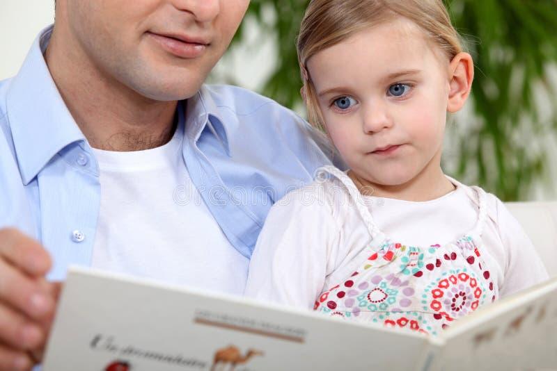 父亲读书女儿故事 库存图片