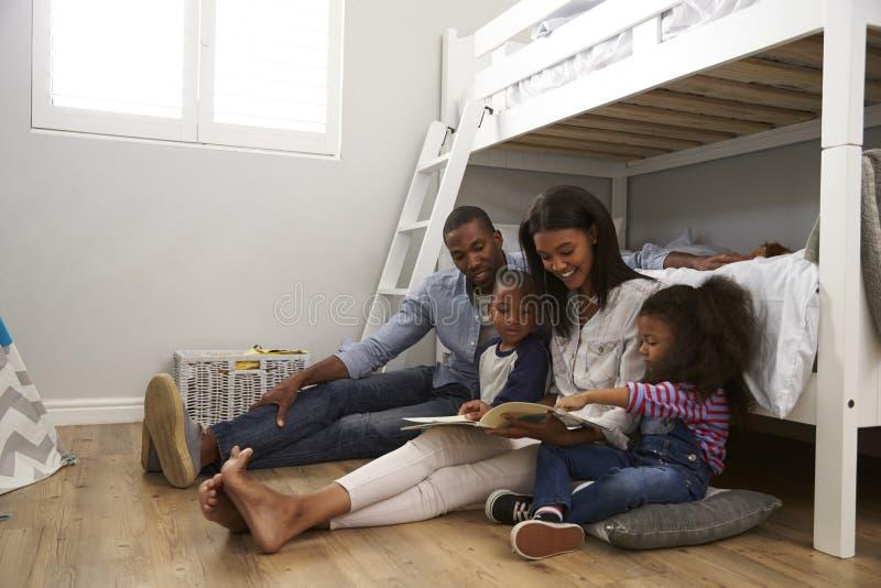 读故事的父母对孩子在他们的卧室 免版税库存图片
