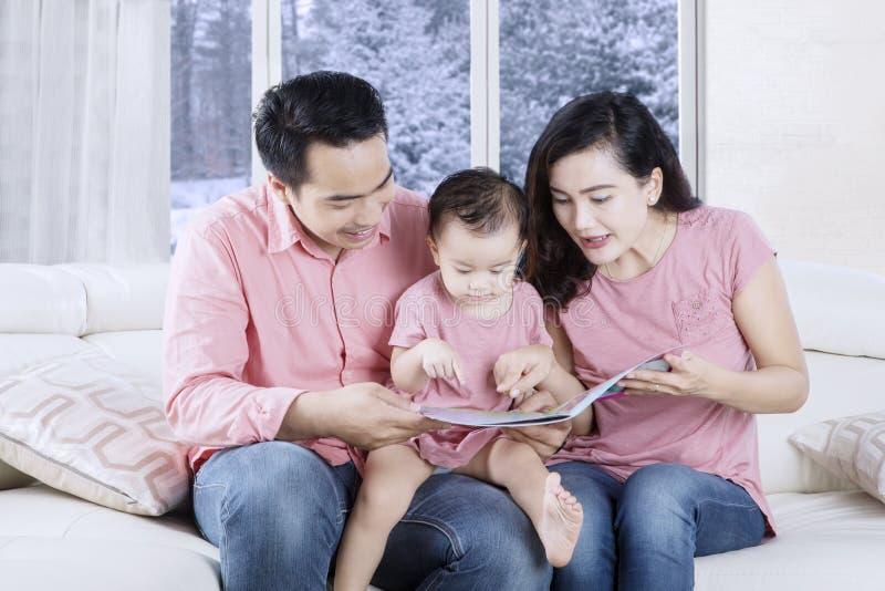 读故事的年轻父母在书 免版税库存图片