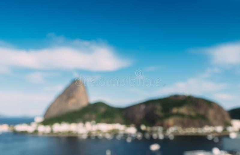 故意地糖面包山和里约热内卢巴西地平线defocused抽象看法反射在博塔福戈海湾的 免版税库存图片