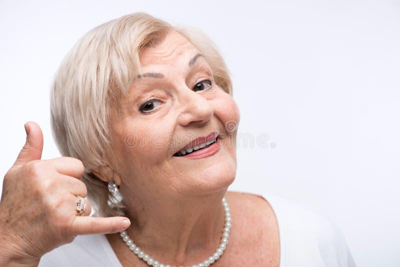仿效电话的愉快的年长妇女 库存照片