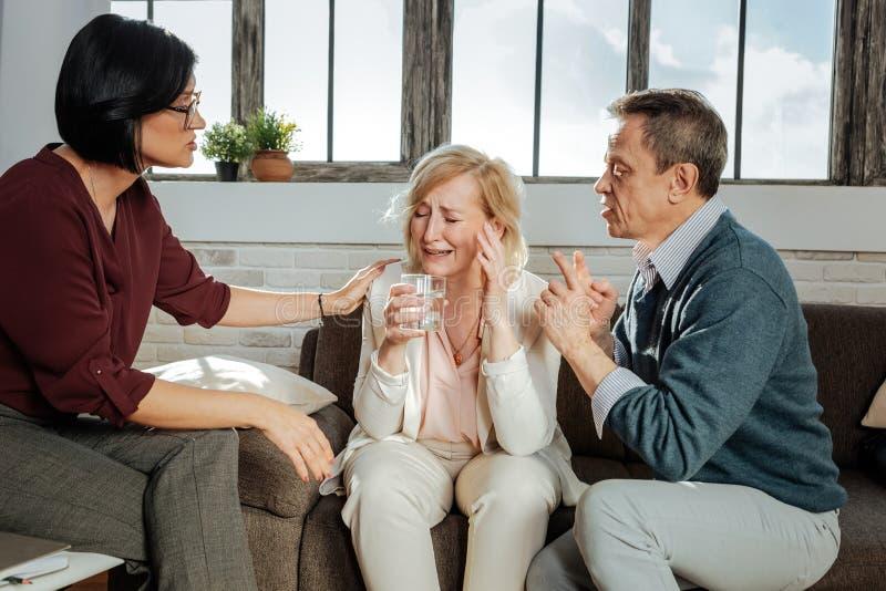 敏感白肤金发的在会议期间的妻子丢失的控制 库存图片