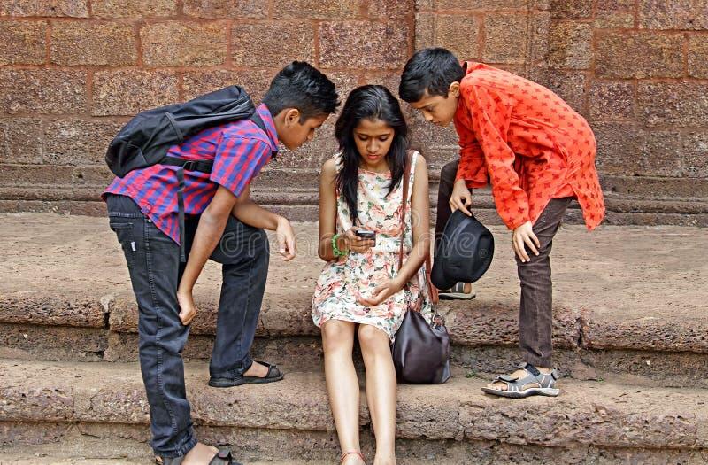 敏锐地观看智能手机的青少年的朋友 免版税库存图片